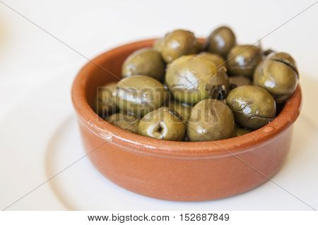 Green crushed marinated olives in clay bowl. Traditional portuguese appetizer