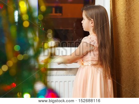 little girl with long brown hair and in pink dress standing at the window at Christmas