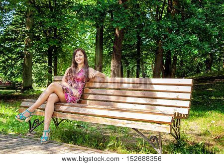 young beautiful girl in bright red dress sitting on a park bench