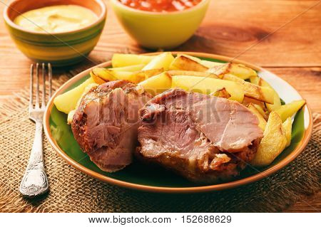 Baked pork knuckle with roasted potatoes .