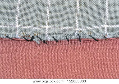Detail of torn textile roughly repaired with a black thread