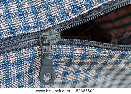 Closeup of a metal zipper and plaid textile