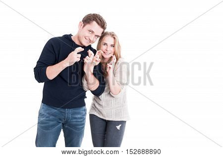 Attractive Couple Showing Fingers Crossed And Smiling