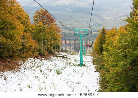 Old chair lift at ski resort. Autumn colored trees and snow.