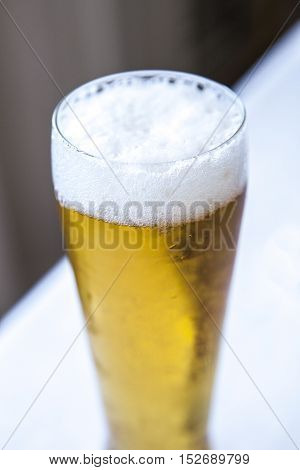 Foamy head on a glass of beer over diagonal dark and white background