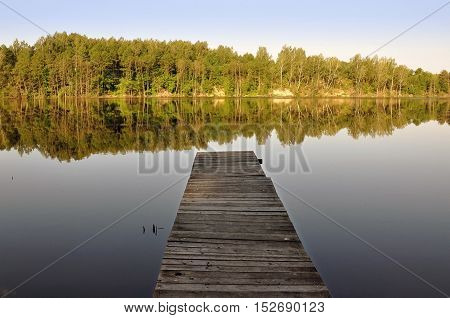 Wooden pier by the river and the forest reflected in water.