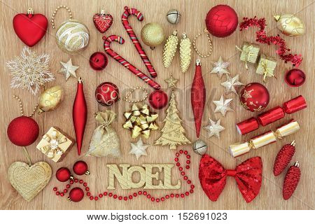 Red and gold christmas tree baubles and decorations with noel sign forming an abstract background over oak wood.