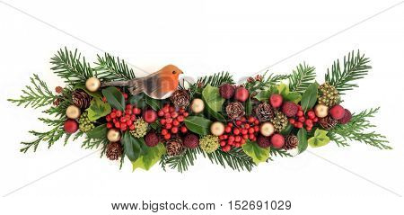 Christmas flora with red and gold bauble and robin decorations, holly, ivy, pine cones , cedar cypress and fir leaf sprigs over white background.