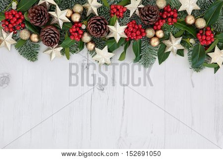 Christmas background abstract border with gold star and round bauble  decorations, holly, ivy, mistletoe, pine cones and snow covered  fir over distressed white wood.