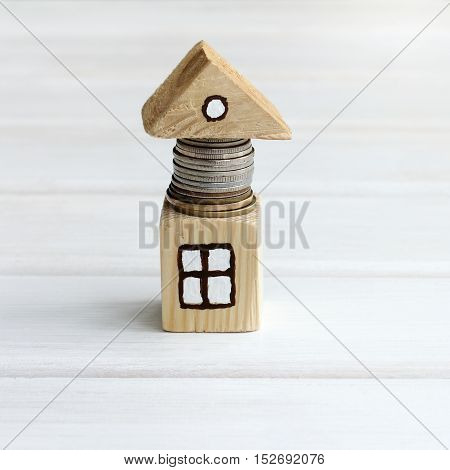 small model of the house with coins located under the roof / profitable investments in real estate