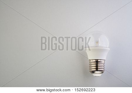 LED lamp with clear bulb on a white surface.