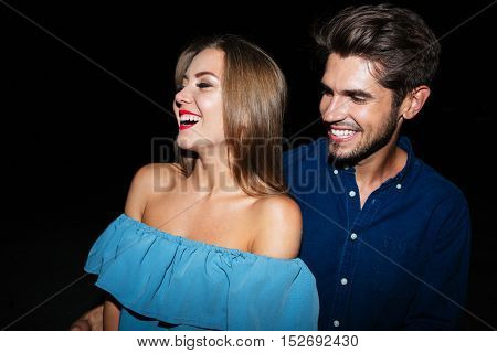 Cheerful young couple standing and laughing together at night