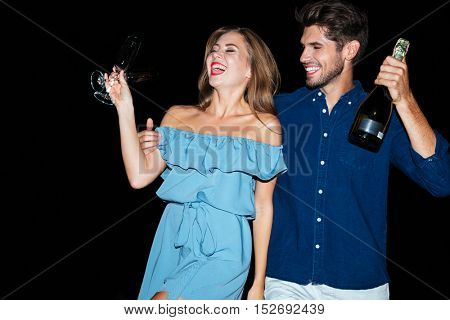 Happy young couple with glasses and bottle of champagne on the beach at night