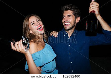 Happy young couple drinking champagne and laughing at night on the beach
