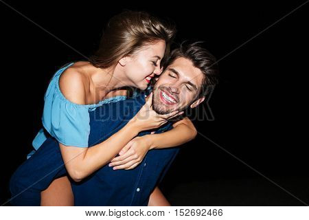 Cheerful attractive young man holding girlfriend on his back at night outdoors