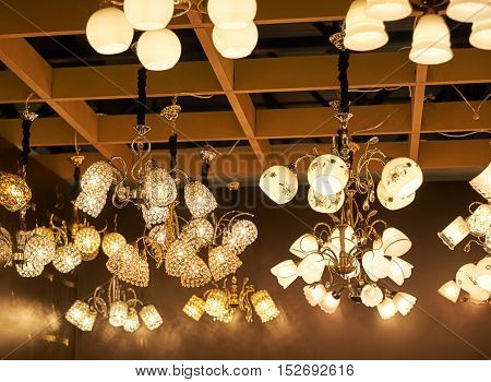 A Lot Of Beautiful Chandeliers With Glass Shades Hanging From The Ceiling In The Sales Area.