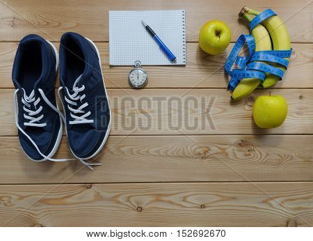Fitness concept with sneakers notebook stopwatch apples bananas and measure tape