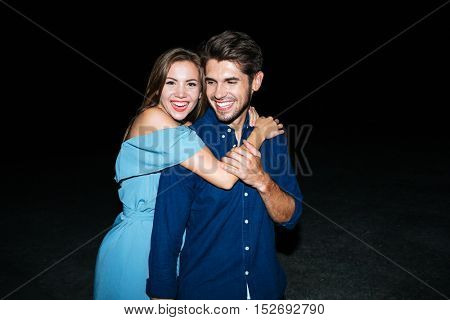 Cheerful young couple stading and hugging on the beach at night