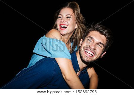 Smiling attractive young man holding girlfriend on his back at night