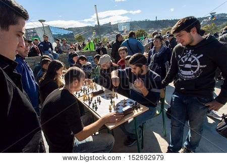 TBILISI, GEORGIA - OCT 16, 2016: Young men playing chess in crowd of players of competition at city festival Tbilisoba on October 16, 2016. Tbilisoba is traditional festival in capital of Georgia from 1979