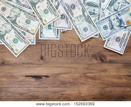 Pile of US dollar bills on old wooden background