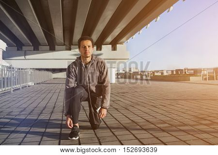 Portrait of fit young black guy tying shoe laces before a run