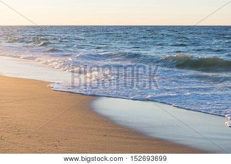 ocean wave on beach sand in sunset light