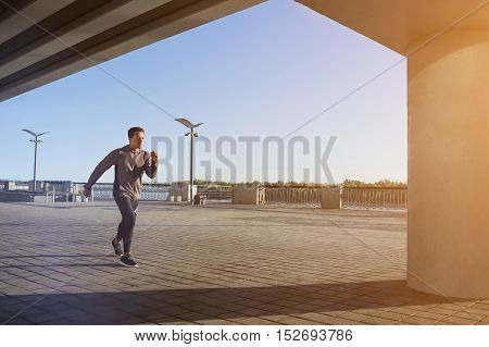 Young fit man in grey windbreaker running at outdoors, autumn running, attractive dark skinned runner jogging fast, sport concept