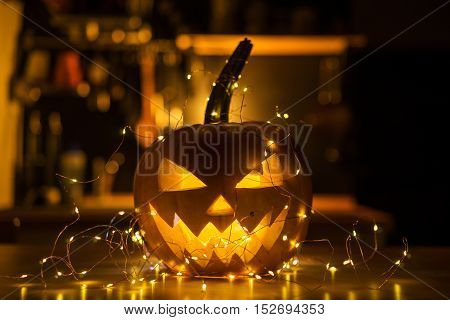 Halloween pumpkin head Jack o' Lantern illuminated on wood table with a garland.