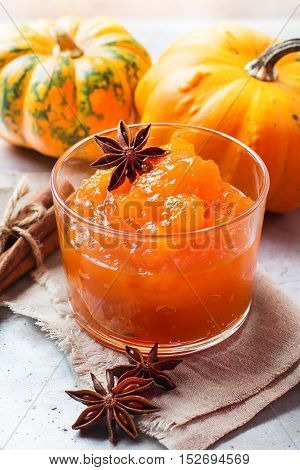Seasonal, food and drink concept. Autumn fall homemade pumpkin jam with spices in glass on rustic table. Selective focus
