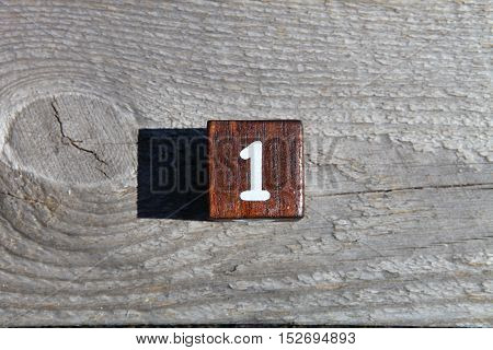 Wooden cube with the number one .