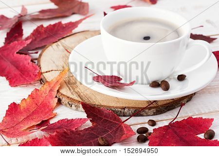 Cup of coffee close-up. Red autumn leaves
