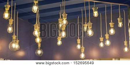 Lamps Of Different Sizes And Shapes. Bulbs Hanging On Wires From The Ceiling.