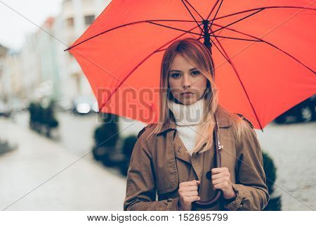 Woman with umbrella. Attractive young woman carrying umbrella and looking at camera while standing on the street