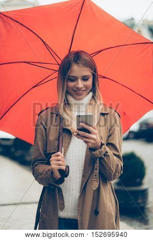 Quick message on the go. Attractive young smiling woman carrying umbrella and looking at her mobile phone while walking by the street