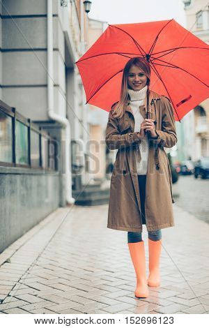 Walking with umbrella. Full length of attractive young smiling woman in colorful rubber boots carrying umbrella and looking at camera while walking by the street