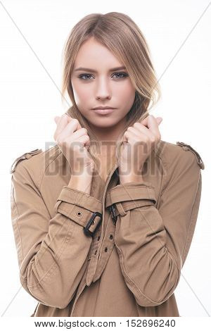 Feeling comfortable and trendy. Attractive young woman in coat adjusting her collar and looking at camera while standing against white background
