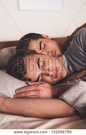 Affectionate young gay couple sleeping arm in arm together in bed in the morning