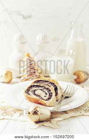 Traditional poppy seed roll cake with icing, dried fruits and nuts (Poland)