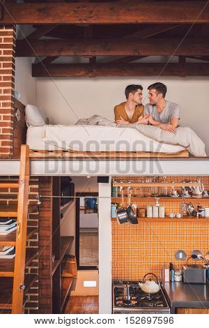 Affectionate young gay couple lying face to face together in their loft bedroom in the morning