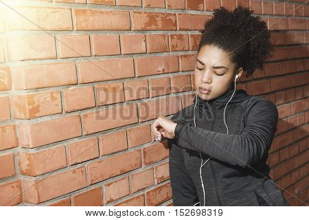 Young woman checking activity tracker after exercise