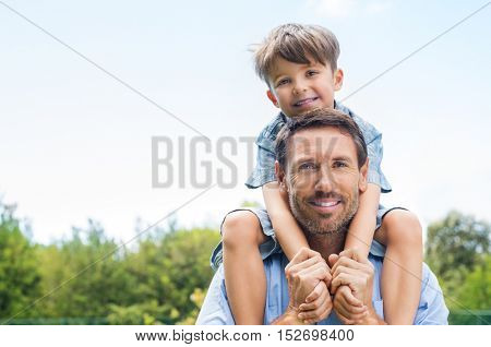 Happy father giving shoulder ride on his shoulders in garden. Happy smiling boy on shoulder dad looking at camera. Father and son enjoying outdoor.