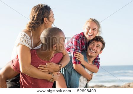 Portrait of two happy young couple enjoying outdoors during summer vacation. Young smiling men giving their girlfriends piggyback rides at sunset.