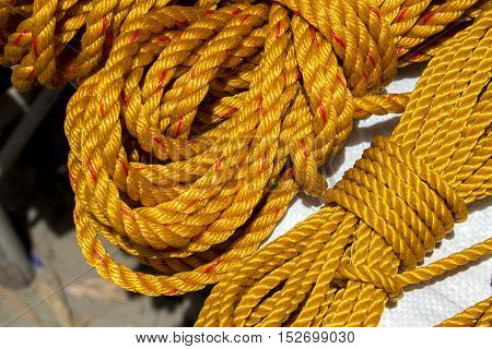 Yellow rope in piles on the market. Braided rope for sailing ship house works construction. Rope bunch image. Horizontal image for houseworks reconstruction DIY project hand tool. Gardening cord