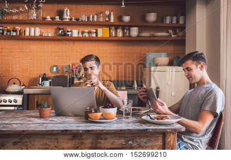 Smiling young gay couple using a digital tablet and laptop while eating breakfast at their kitchen table in the morning