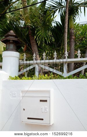 House mailbox mounted on a white villa fence. Postbox hanging on a wall of green tropical yard with palm trees