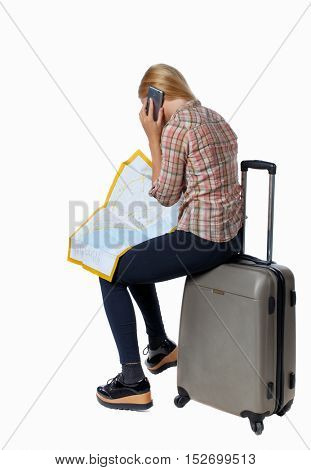 back view of woman traveler sitting on their suitcases and looking for a route map, talking on the phone. Isolated over white background. Girl with very long hair trying to find his way.