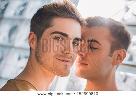 Portrait of an affectionate young gay couple standing close together at home