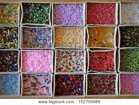 Many kinds of beads of different colors and shapes in cardboard boxes. Background top view.