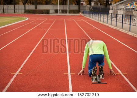 Young sporty man are ready to run on racetrack. Fit well formed people are at large nice modern stadium